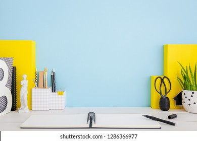 School desk with box, notebook, statuette and blue wall.