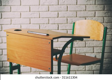 School desk and chair on white brick wall background