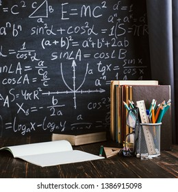 School desk in the classroom, with books on background of chalk board with written formulas. Soncept Teachers Day.