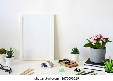 School desk on a white wall. School supplies, pencils, book and notebook, plants, glasses and pink flowers. Copy space. White mockup frame.