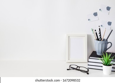 School desk on a white wall. School supplies, mug with pencils, books and notebooks, plant, glasses and sticky notes. Copy space. White mockup frame.