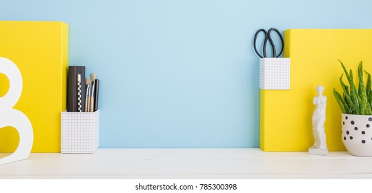 School desk with a stationery, plant and pencils on a blue background