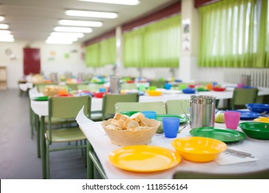 School dining room tables prepared for children to eat with glasses, plates, jugs.