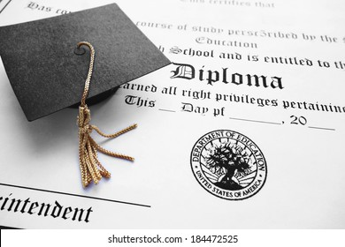 School diploma and mini graduation cap