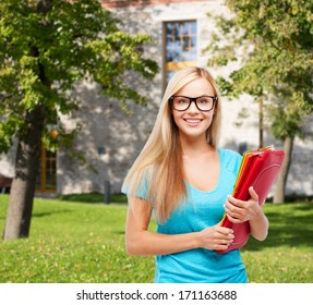 school and education concept - smiling student in eyeglasses with folders