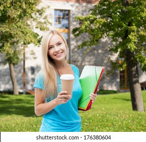 school and education concept - smiling student with folders and cup of coffee
