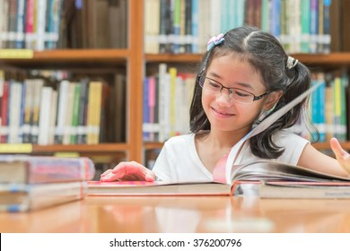 School education and literacy concept with Asian girl kid student opening and reading children's picture book happily in library or classroom