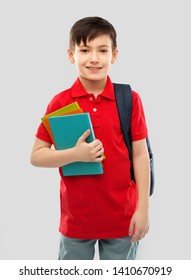 school, education and people concept - portrait of smiling little student boy in red polo t-shirt in glasses with books and bag over grey background