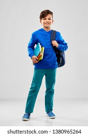 school, education and people concept - smiling student boy with books and bag over grey background