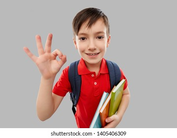 school, education and people concept - smiling little student boy in red polo t-shirt in glasses with books and bag showing ok hand sign over grey background