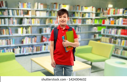 school, education and people concept - smiling little student boy in red polo t-shirt in glasses with books and bag over reading room of library background