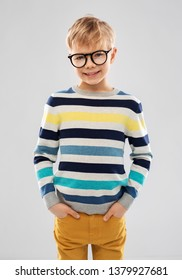 school, education and vision concept - portrait of smiling little boy in striped pullover and glasses over grey background