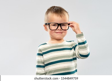 school, education and vision concept - portrait of smiling little boy in glasses over grey background