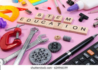 School equipment with word STEM Education over pink background in education STEM concept. School desk with stationery tools for STEM learning.