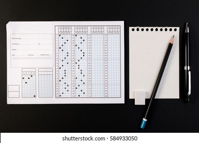 School exam answer sheet and pen. Standard test form or keyword sheet. Answer sheet focus on pencil. Bubble answer sheet with blank answer.