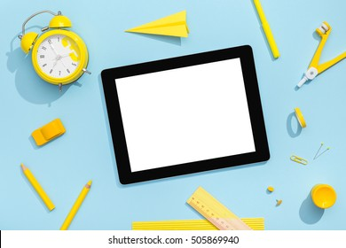 School fashion. Blank tablet with school and office tools on office table. Flat lay with copy space. Back to school concept.