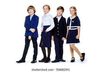 School fashion. Group of happy children in school uniform posing at studio. Isolated over white background. Copy space.