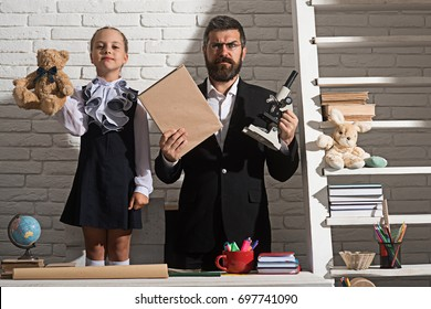 School and fathers day concept. Girl and dad on white brick background. Schoolgirl and man with proud and confused faces hold toy bear, book and microscope. Family stands by desk with school supplies