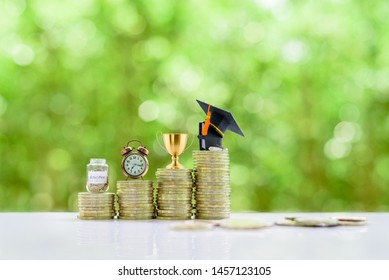 School funding, saving for higher education concept : Black graduation cap, campus diploma, trophy cup of success or winner reward, clock, a saving jar on rising coins, depicts passage way of success