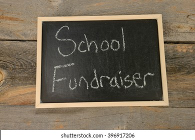school fundraiser written in chalk on a chalkboard on a rustic background