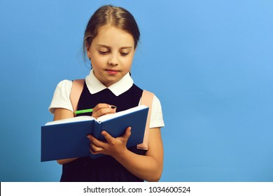 School girl with attentive face expression on blue background. Girl does homework writing in blue notebook, copy space. Back to school and education concept. Pupil in school uniform with book