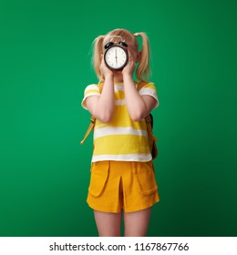 school girl with backpack holding alarm clock in the front of face against green background