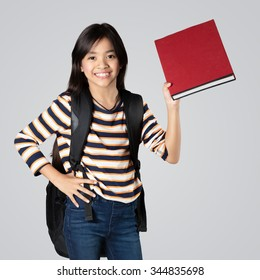 School girl with a backpack  shows a book and smiles, Isolated on grey background