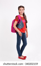 school girl with a backpack standing in jeans on a white background and smiling.