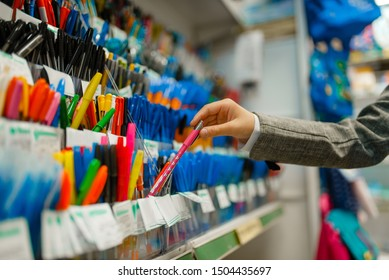 School girl choosing a pen in stationery store
