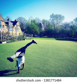 School girl doing cartwheels on school field.