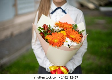 School girl dressed in school uniform holding a bright pink festive bouquet of beautiful flowers for teacher. No face. Blurred background.