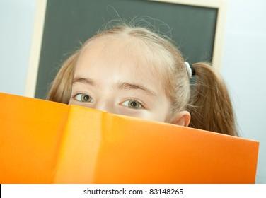 School girl hiding behind yellow book
