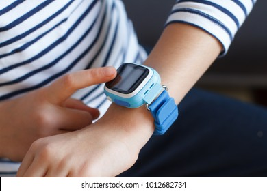 School girl looking at her smart watch phone. Time clock.