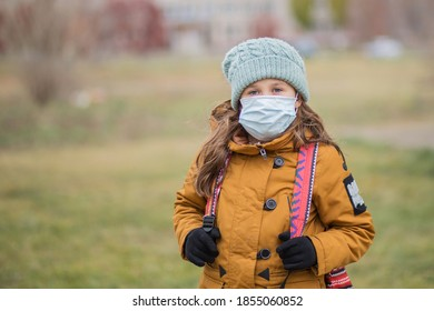 School girl in medical mask with bagpack. At atumn city