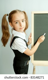 School girl near blank blackboard. Ready for writing.