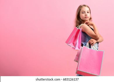 School girl with packages isolated on pink background, copy space. Girl with pink shopping bags. Sale and fashion concept. Kid with confident face expression and casual hairdo does shopping