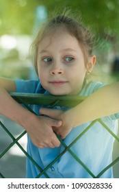 School Girl Playing on Metal Bars Fence School Yard Summer Blurred Background