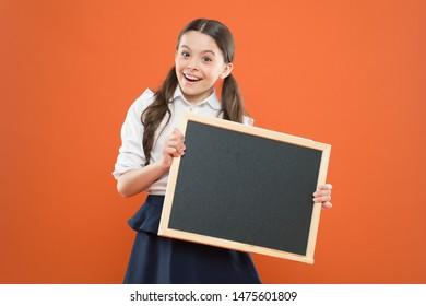 School girl pupil hold blackboard copy space.