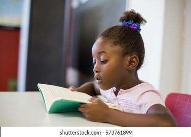 School girl reading book in classroom at school