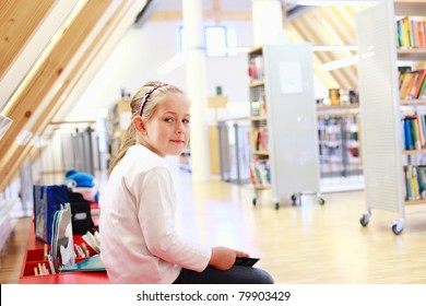 School girl reading a book in library