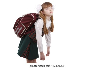 School girl is tired. Schoolgirl in school uniform with backpack. Pupil's satchel is very heavy.  Sad teenager. A heavy load to bear. Isolated on white in studio.
