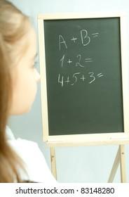 School girl view on the blackboard. Back view.