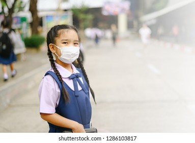 School Girl  wearing mouth mask against air smog pollution in Bangkok city, Thailand.