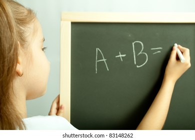 School girl write exercise on the black board in the class