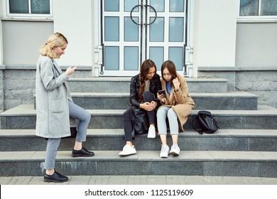 school girls sitting on the steps using smartphones. Students near university