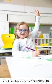 At school - Happy schoolchild raising hand in classroom