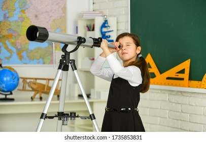 School hobby club. Observation concept. Astronomy and Astrophysics. Stars and galaxies. Study telescope. School astronomy lesson. School girl looking through telescope. Telescope tripod in classroom.