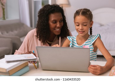 School home task. Delighted nice woman smiling while helping her daughter with the home task