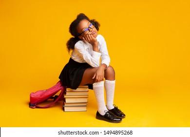 School Homework Concept. Bored Afro Schoolgirl Sitting On Stack Of Books Over Yellow Studio Background. Empty Space