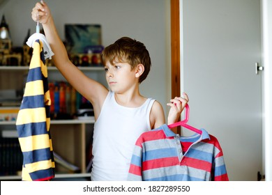 School kid boy standing by wardrobe with clothes. Child making decision for school shirt to wear. Children get dressed in the morning for school.